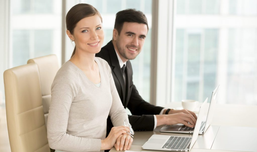 Smiling professional businesswoman and businessman with laptops
